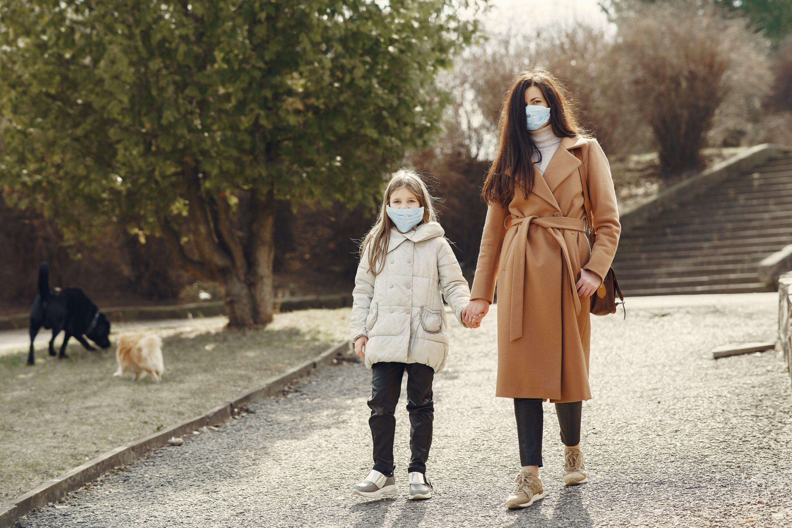 Mother and daughter walking together with masks on