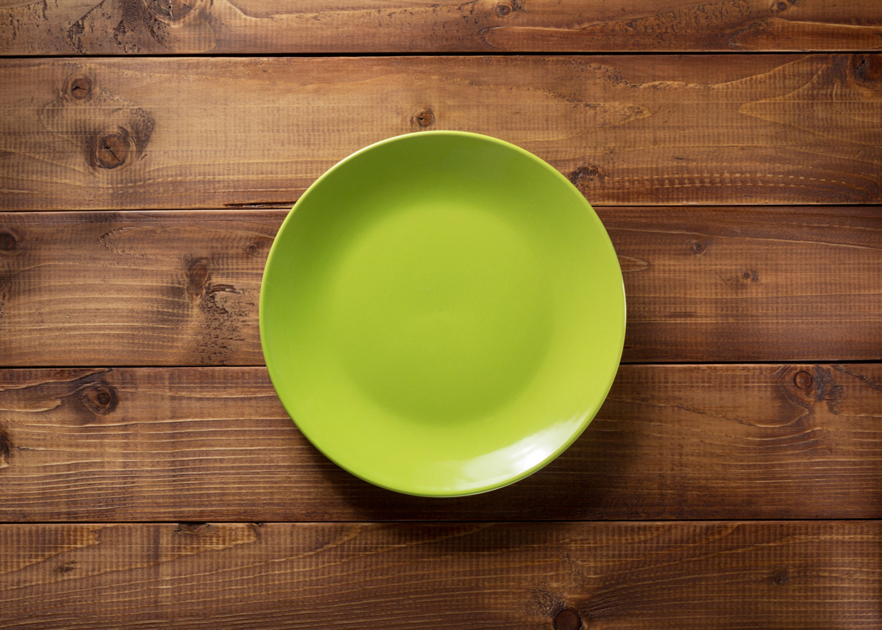 Green plate on table in hygienic restaurant
