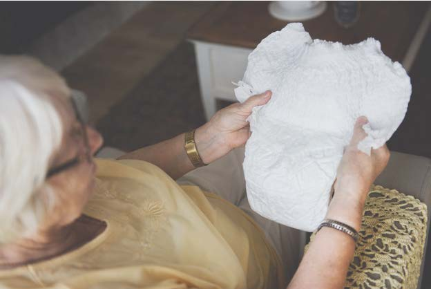 Elderly woman looking at an adult diaper