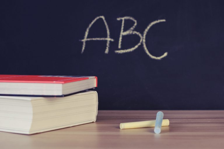 Books and a chalk black board with 'ABC' written
