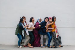 diverse women laughing in front of a white wall
