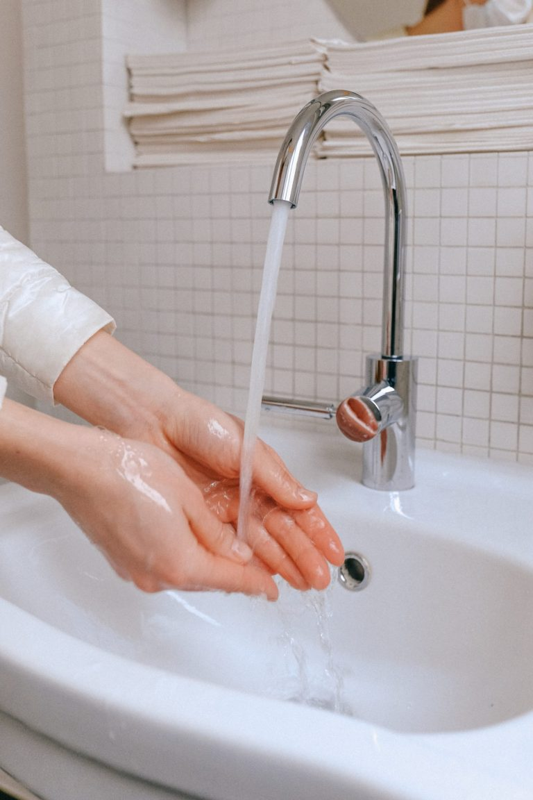 Lady washing her hands with soap and water