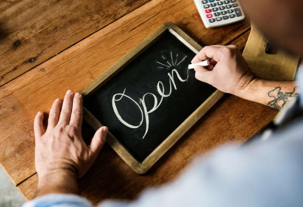 Man writing an 'Open' sign for his business